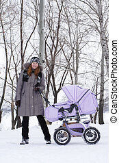 winter walk - young smiling mother with perambulator on a...