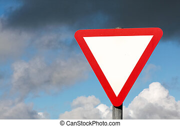 Give way sign without text and dark clouds in Ireland
