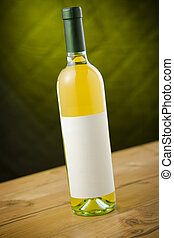 White wine bottle on wooden table over dark green yellow...