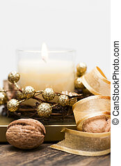 Festive candle surrounded by nuts and tape.