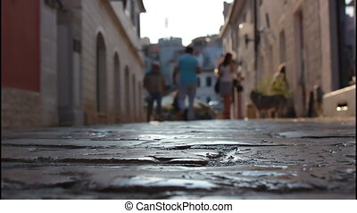 Street made of stone, people walking down the street, girls