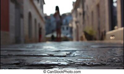 Street made of stone, people walking down the street, woman...
