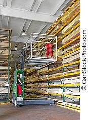 Forklift platform basket - Workers handling plank boards in...