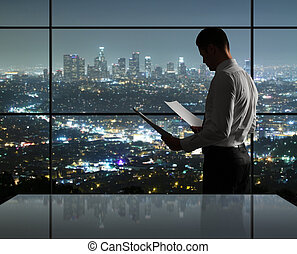 man in night office - businessman standing in night office