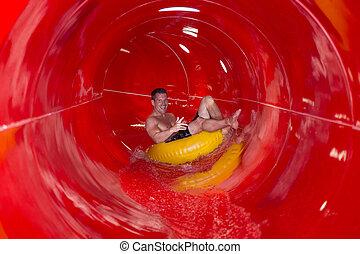 Man having fun sliding down a waterslide in public swimming...