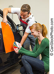 Car branding specialist consults a client about adhesive foils or films for auto wrapping
