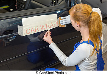 Car wrapping specialist puts logo on vehicle door