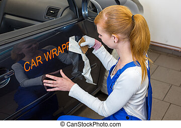 Car branding specialist puts logo with car wrapping film on automobile