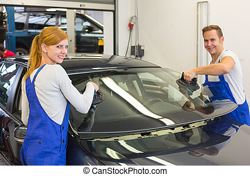 Mechanics or glaziers install windshield or windscreen on...
