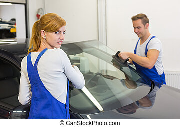 Mechanics or glaziers install windshield or windscreen on car