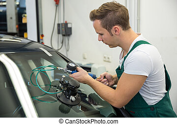 Glazier repairing stone-chipping damage on car's windshield...