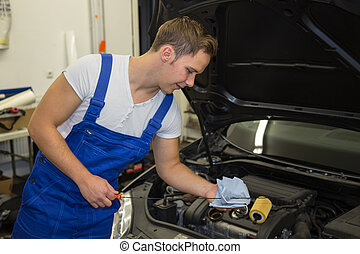 Mechanic in garage checking motor oil level at a car -...