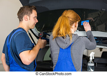 Mechanic tinting car window with tinted foil or film
