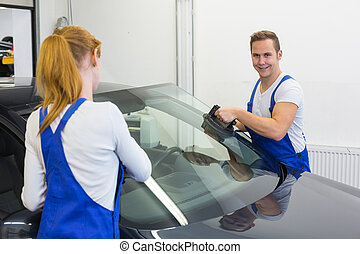 Glaziers replace windshield or windscreen on car after...