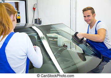 Two glaziers or mechanics replace windshield or windscreen on car