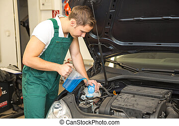 Mechanic fills coolant or cooling fluid in motor of a car -...