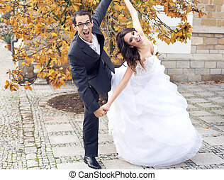 Laughing wedding couple in funny pose