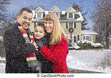Mixed Race Family in Front of House in The Snow - Happy...