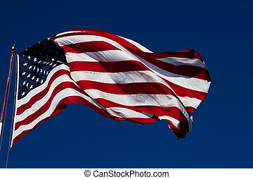 windy us flag - windy day clear blue skies with American...