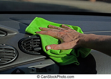Dashboard dusting - A man dusting a dashboard of a car with...
