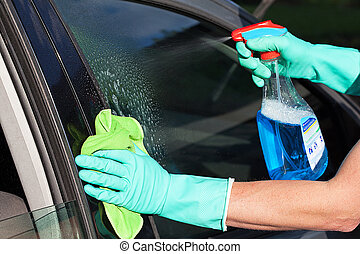 Car window washing - A man washing a car's window using a...