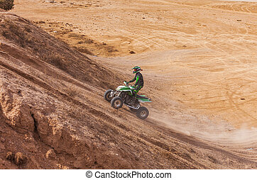 ATV rider uphill in the desert in summer