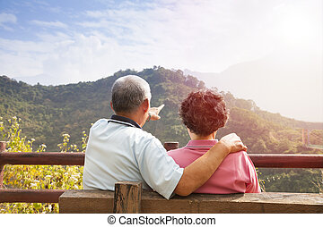 senior couple sitting on the bench looking the nature view