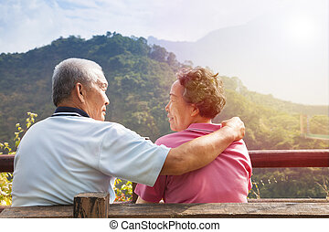 senior couple sitting on the bench in nature park