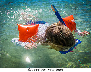 Child Snorkelling - A Child Snorkelling In A Tropical Ocean