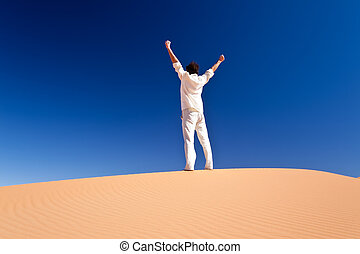 Man standing on a sand dune - Rear view of a adult white man...