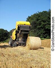 Baler discharging a bale - A baler discharges a round wheat...