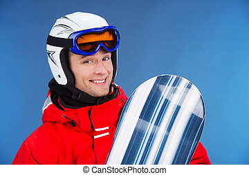 Close up of smiling male snowboarder in helmet and mask. Standing with snowboard isolated over blue background