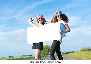 Two young women stand with a blank banner on the side of the...