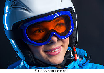 Portrait of happy smiling sportswoman with beautiful eyes in helmets. Standing isolated over black background