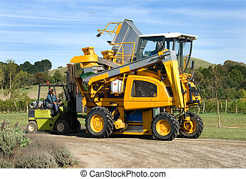 Vineyard Machinery - A grape harvester unloading grapes into...