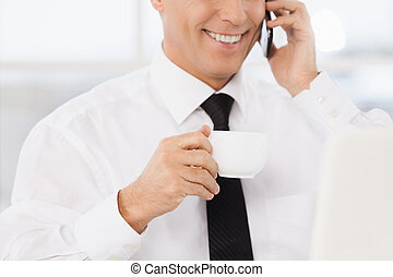 Cheerful businessman. Cropped image of smiling mature man in formalwear drinking coffee and talking on the mobile phone while sitting at his working place