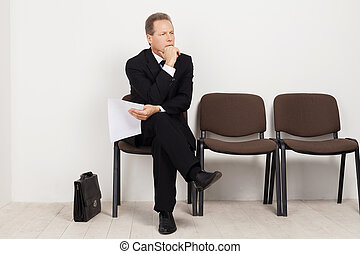 Job candidate. Bored mature man in formalwear holding paper...
