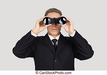Looking for the new opportunities. Confident mature man in formalwear looking through binoculars while standing against grey background