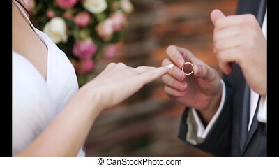Dressing wedding ring - The bride groom wears wedding ring...