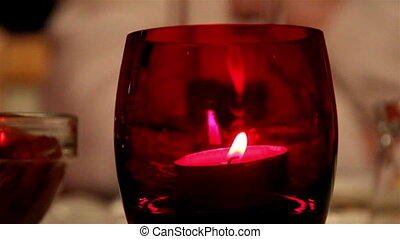 A candlelight inside a red glass - A closer look of a...