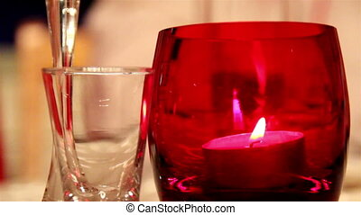 A candlelight inside a red glass and a small glass beside it