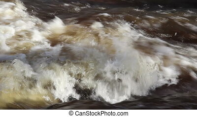 Rapids of water creating bubbles on the river