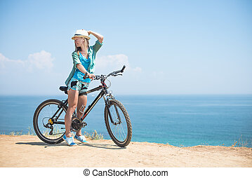 Attractive woman with bike at the sea