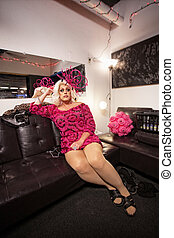 Man in Dress Relaxing - Man in dress and wig sitting in a...