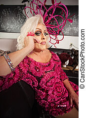 Blond Drag Queen Sitting - Blond drag queen in pink dress...
