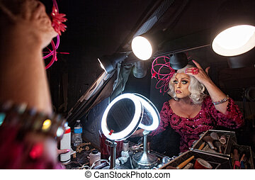 Man Fixing Hair in Mirror - Female impersonator adjusting...