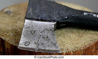Some water droplets are falling on the axe while lying on...