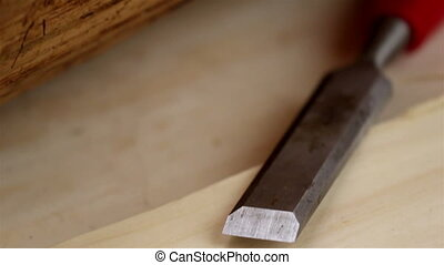 A 14mm red chisel beside a wooden lumber