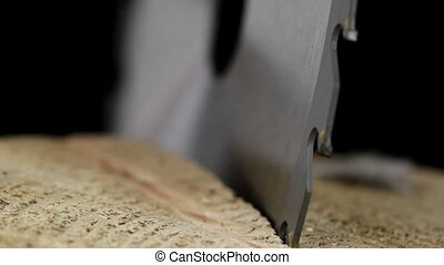 A saw blade stuck on the wood - A saw blade with sharp edges...