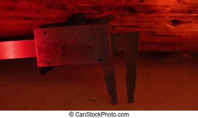 Side view of a caliper under a red-lighted room